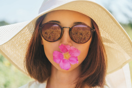 brim: Portrait of beautiful woman in sunglasses and hat with wide brim with flower, concept of happiness and summer mood Stock Photo