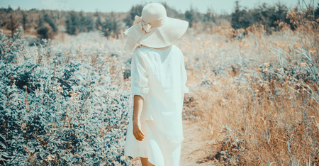 brim: Young woman in dress and hat with wide brim walking in summer fairy beautiful park, rear view Stock Photo