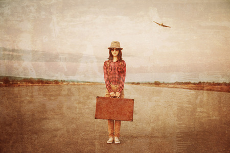 Traveler woman stands on road with vintage suitcase, airplane in sky. Space for text. Vintage image photo