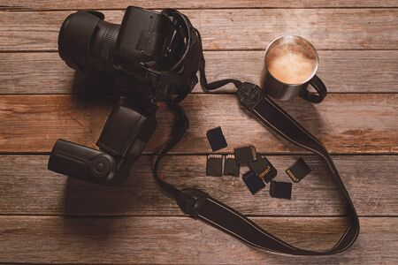 digital memory: Digital photo camera, memory cards and cup of coffee on wooden table Stock Photo