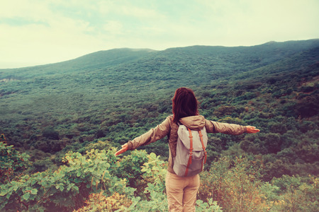Freedom traveler woman standing with raised arms and enjoying a beautiful nature. Image with instagram filter