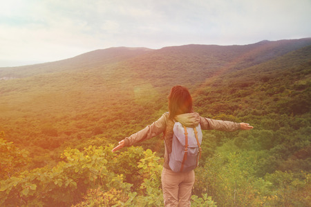 Freedom traveler woman standing with raised arms and enjoying a beautiful nature. Image with sunlight effect Standard-Bild