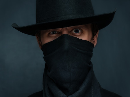 buckaroo: Man cowboy is surprised with a scarf on his face and in a black hat