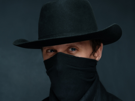buckaroo: Portrait of a man cowboy with a scarf on his face and in a black hat