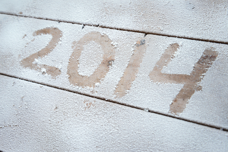 2014 written in snow on a wooden background photo