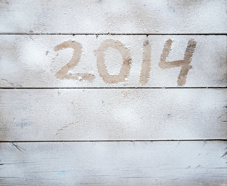 2014 written in snow on a wooden table photo