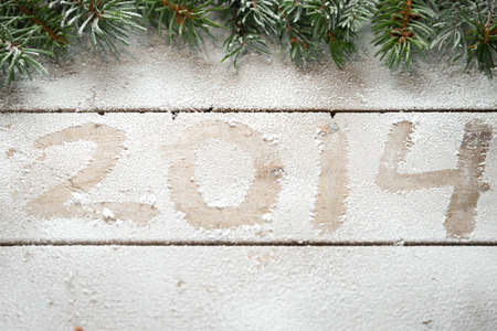 Branches of Christmas tree above the inscription 2014 in the snow photo