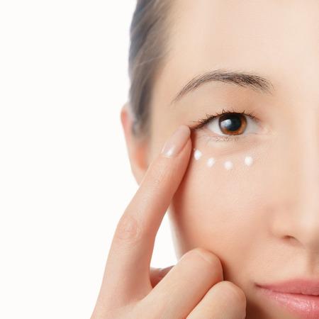 ojos marrones: Retrato de mujer hermosa, aplicación de crema en la piel alrededor de los ojos
