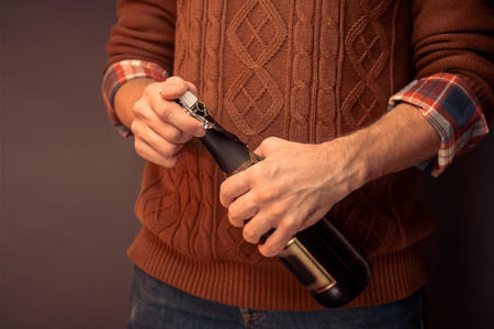 unrecognizable: Unrecognizable man in sweater is opening champagne, close-up Stock Photo