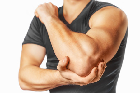 Man holds his the elbow joint, acute pain in the elbow. photo