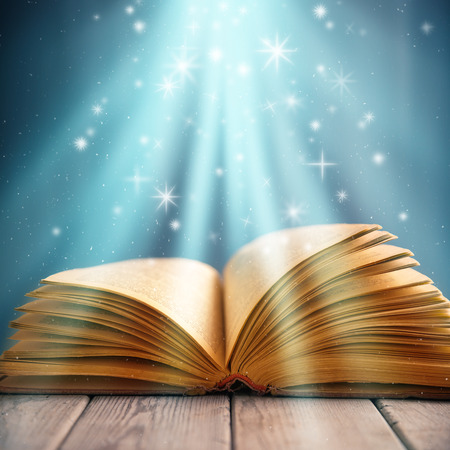 The open old book under magic light on a wooden table