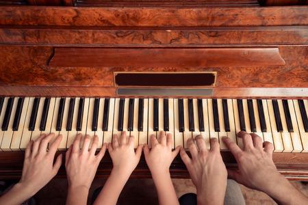 tocando piano: Familia de tres personas que juegan el piano. Punto de vista de tiro