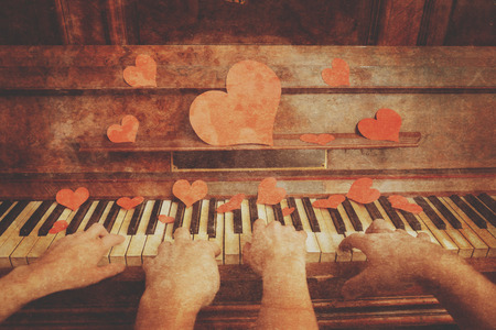 old piano: Couple is playing on piano on Valentines Day, close-up, face is not visible. Vintage image