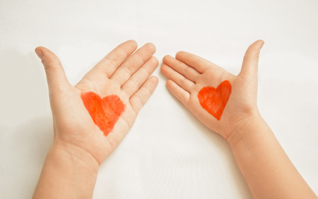 child care: Hands of mother and child painted with red hearts, concept of love
