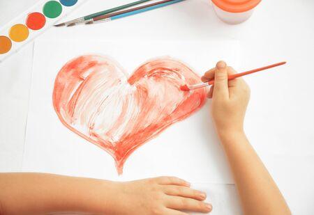 unrecognizable: Unrecognizable child paints red heart Stock Photo
