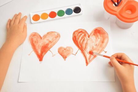 unrecognizable: Unrecognizable child paints three red hearts, concept of family
