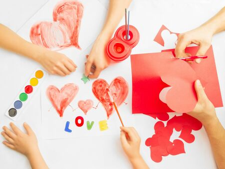 Family prepare for Valentines Day. Paintings and origami of heart. Concept of family photo