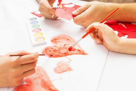 Mom and Dad help the child paint heart. Concept of family photo