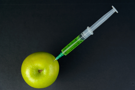injected: Green liquid in the syringe injected into green apple, top view
