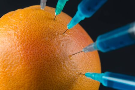 injected: Blue liquid in the syringe injected into grapefruit, close-up Stock Photo
