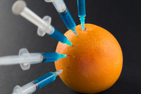 injected: %u0421hemical liquid in the syringe injected into grapefruit on a black