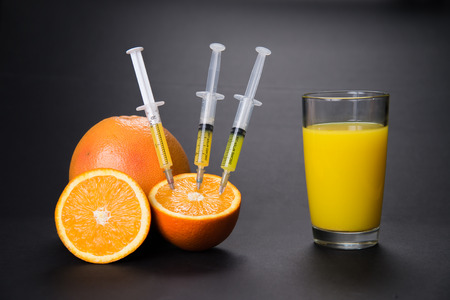 Syringes pumped out vitamins from an orange to juice