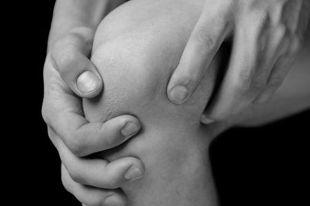 O homem está pegando a articulação do joelho devido à dor aguda Banco de Imagens
