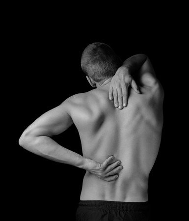 muscular man: Man is touching the back, concept of pain in the spine, monochrome image