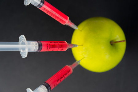 injected: Red liquid in the syringe injected into green apple, top view Stock Photo