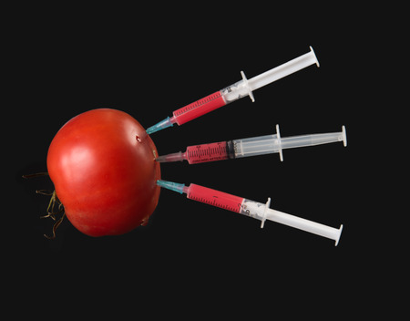 injected: Red liquid in the syringe injected into tomato on a black , side view Stock Photo