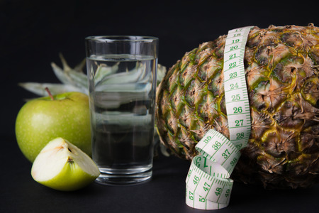tapeline: Fruits and glass of water with a measuring tape, concept of diet Stock Photo