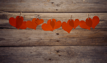 hangs: Red paper hearts hangs on clothespins on a wooden  Stock Photo