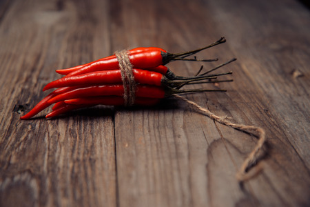 chili peppers: Chili peppers in a bunch shaped like a bomb with a wick on a wooden table Stock Photo