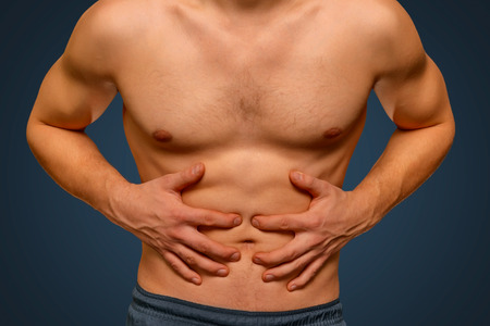 hombres sin camisa: Hombre irreconocible comprime el abdomen debido al dolor Foto de archivo