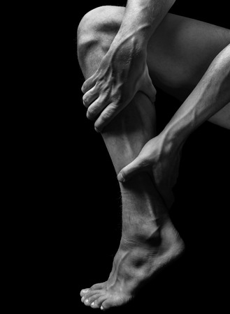 acute care: Acute pain in the male calf muscle, black and white image Stock Photo