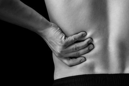 O homem toca a parte inferior das costas, dor nos rins, imagem monocrom