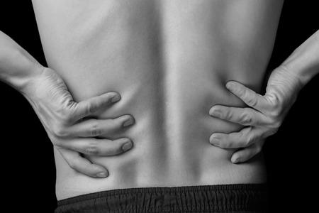 Akutní bolest v dolní části zad muže, černý a bílý obraz