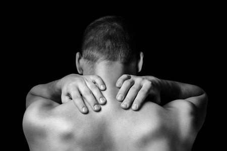 Nierozpoznany mężczyzna dotyka szyi, bóle szyi, widok z tyłu