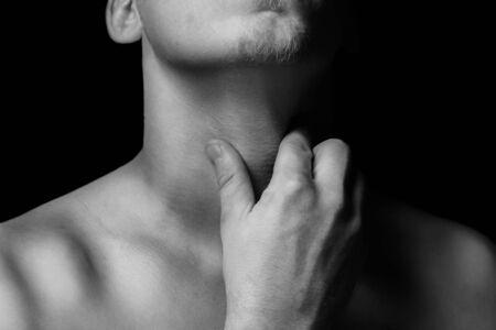 tonsillitis: Man holds the throat, sore throat, monochrome image