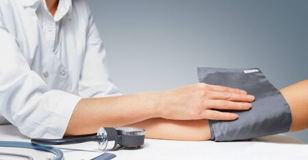 sphygmomanometer: Doctor puts cuff of sphygmomanometer on the patients arm