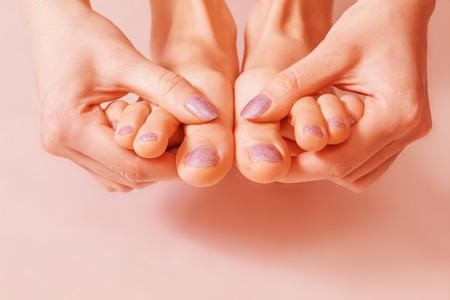 uñas pintadas: La mujer muestra sus uñas y dedos de los pies pintadas