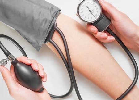 hypotension: Unrecognizable doctor measures blood pressure a patient, top view