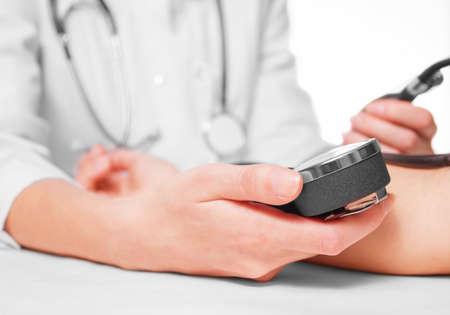 hypotension: Unrecognizable doctor measures blood pressure a patient, side view