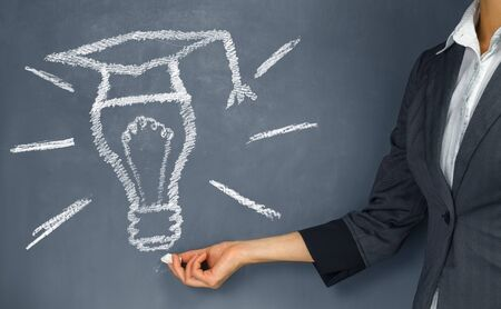 learning concept: Unrecognizable woman points to the light bulb in a hat, concept of new idea and education Stock Photo