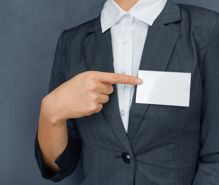 name badge: Unrecognizable businesswoman indicate to namecard on the chest, copyspace