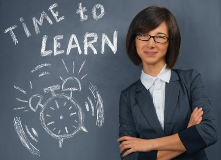 business attire teacher: Young woman stands near blackboard with text time to learn