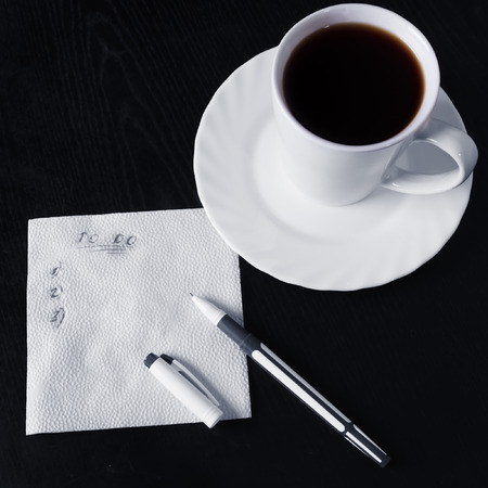 do: List to do, cup of coffee and pen on black table Stock Photo