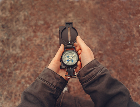 compass: Female traveler holding a compass on nature. Point of view shot