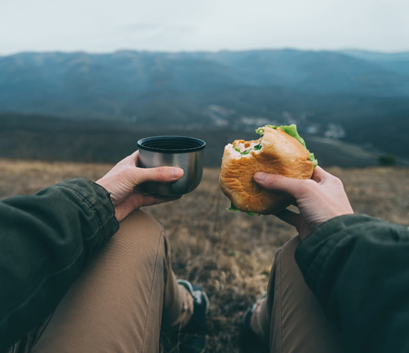 point of view: Traveler woman have lunch on nature. Point of view shot Stock Photo
