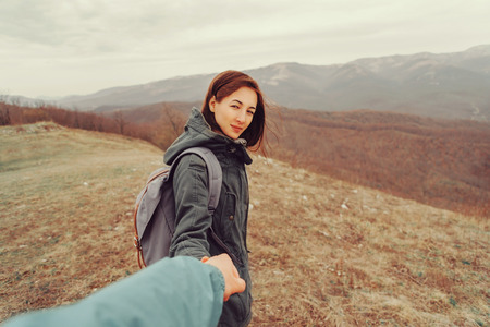 point of view: Traveler woman holding mans hand on nature in the mountains. Couple in love. Focus on woman. Point of view shot Stock Photo